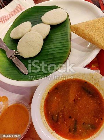 South Indian vegetarian dish Idli Sambar/Saambar/Sambhar/Saambhar  plated over a banana leaf. Focus on Bowl of Sambhar. A bit of dosa trying to sneak into the appetising menu. Mouth watering chutney alongside. Depth of field.