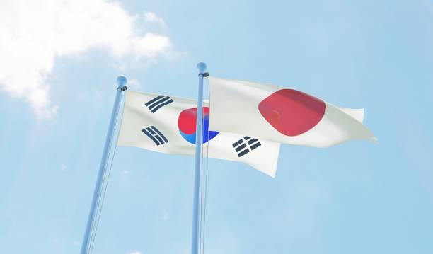 韓国と日本、青い空を背景に手を振っている 2 つのフラグ - 韓国 ストックフォトと画像