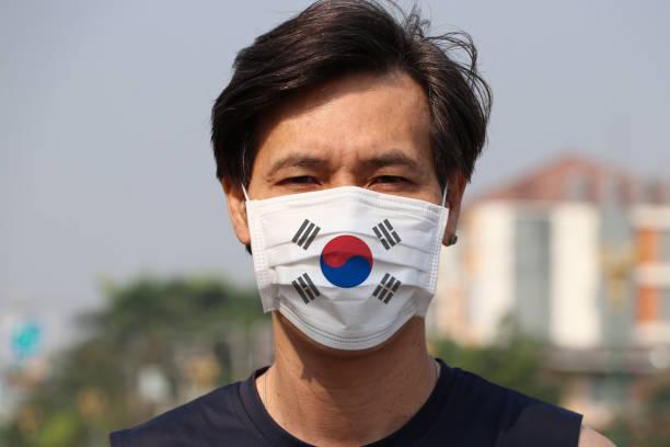 衛生的なマスクに韓国の旗。仮面を被ったアジア人は細菌を防ぐ。タイニー粒子保護の概念。 - 韓国 ストックフォトと画像