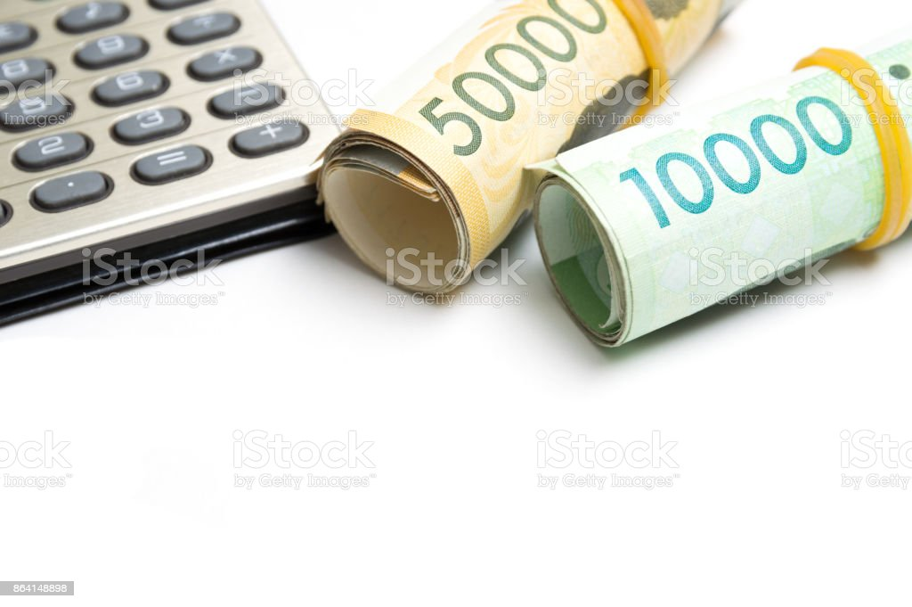 South Korean won currency tied rubber band and calculating machine on white background royalty-free stock photo
