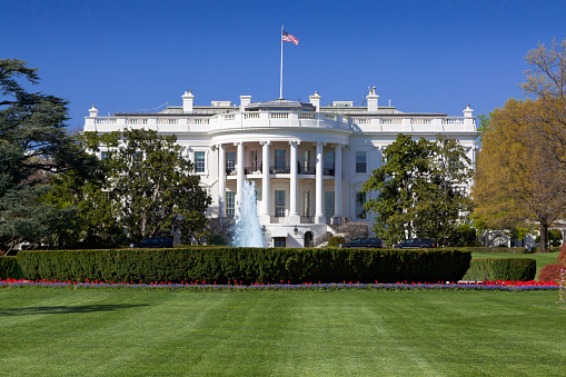 The South Portico of the White House. Washington DC. The White House is the official residence and principal workplace of the President of the United States, located at 1600 Pennsylvania Avenue. Beautifully landscaped lawn with flowers, fountain and blooming trees is in foreground. Deep blue clear sky is in background. American flag is flying atop. The image lit by spring evening sun. Canon 24-105mm f/4L lens.