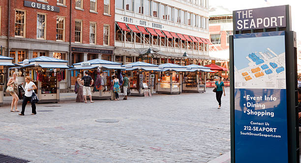 South Street Seaport New York City New York, New York, USA - June 2, 2011: People stroll along this cobblestone section of Fulton Street in The South Street Seaport district in New York City. This once vital port is now a touristy area and has many shops and restaurants. It dates back to the early days of New York. Focus is on the Seaport sign. south street seaport stock pictures, royalty-free photos & images