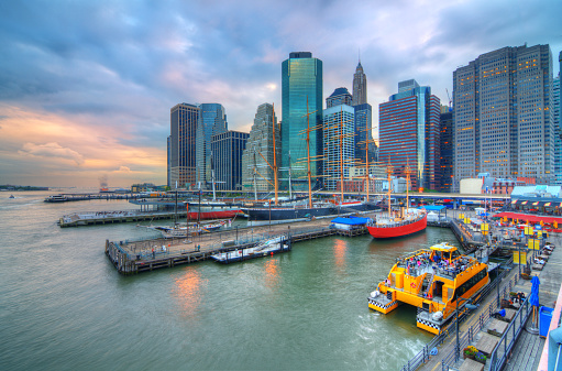 The historic district of South Street Seaport juxtaposed against the imposing Financial District skyscrapers in New York City.
