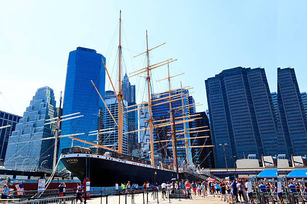 South Street Seaport New York, NY, USA - July 6, 2014: South Street Seaport and The Peking: The South Street Seaport is a historic area in the New York City borough of Manhattan, centered where Fulton Street meets the East River, and adjacent to the Financial District. The Peking is a steel-hulled four-masted barque.  south street seaport stock pictures, royalty-free photos & images