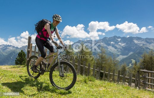 A female mountainbiker is crossing an alpine pasture nearby the village of Sand in Taufers at Valle Aurina (germ. Ahrntal) in South Tyrol. This valley is a side valley of the Pustertal (ital. Valle Pusterino) in northern Italy. The region is famous for the scenic landscape.