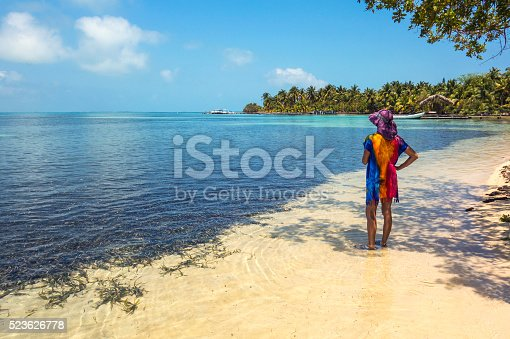 Woman on the lee shore beach of South Water Caye. Belize Caribbean.