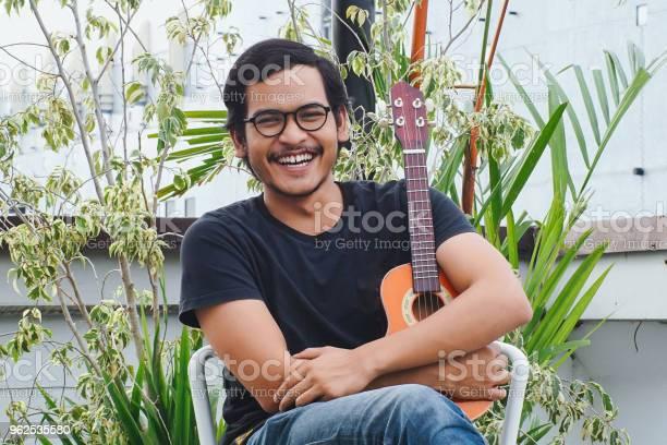 Foto de Sudeste Asiático Homem Tocando Cavaquinho e mais fotos de stock de Adulto