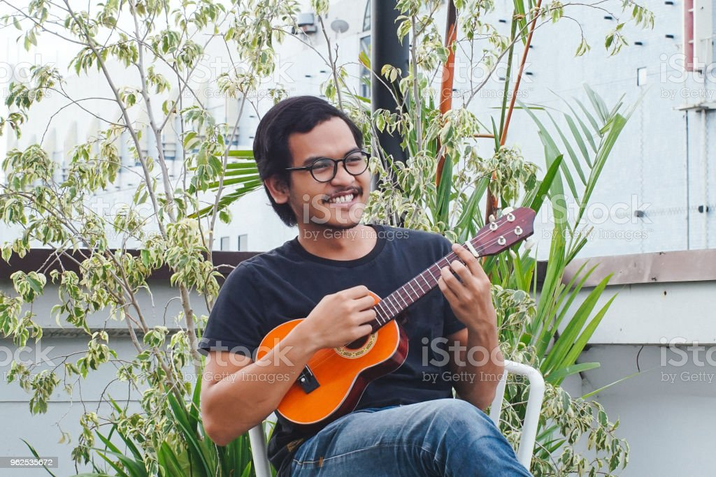 Southeast Asia Man Playing Ukulele - Royalty-free Adult Stock Photo