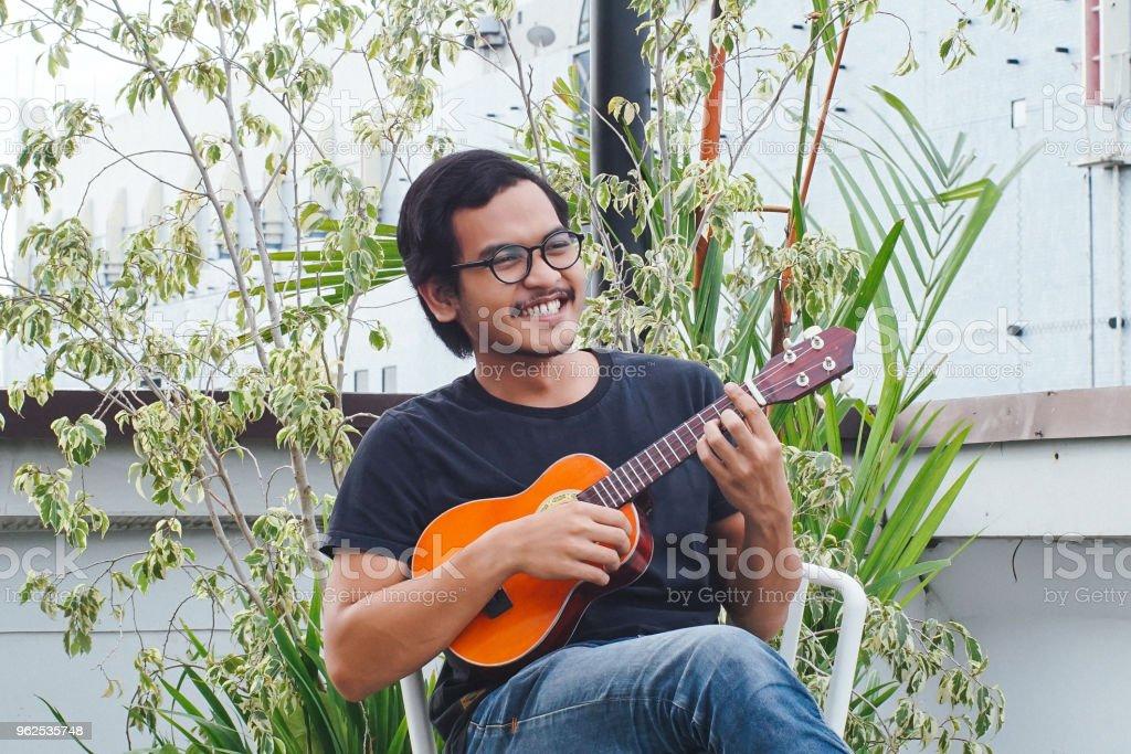 Southeast Asia Man Playing Ukulele - Royalty-free Adult Stock Photo