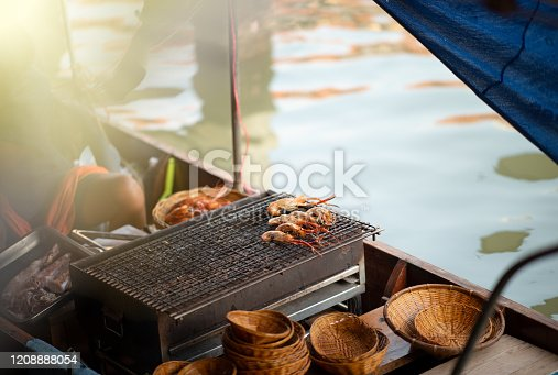 Southeast Asia. Travel. Culture and traditions Grilled fish along the river at Amphawa floating market. Bangkok. Thailand.