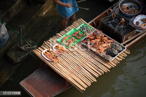 Southeast Asia. Travel. Culture and traditions. Little girl with legs in  water checking fish on the grill along the river at Amphawa floating market. Bangkok. Thailand.