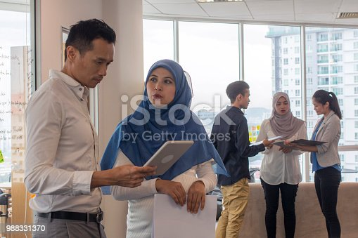 multiracial colleagues discussing over digital tablet while another group standing over a couch in a creative office in Malaysia
