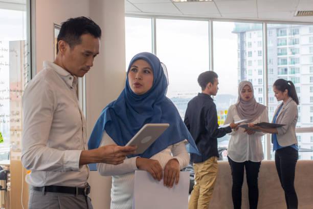 近代的なオフィスに東南アジア民族事務所スタッフミーティング - business malaysia ストックフォトと画像