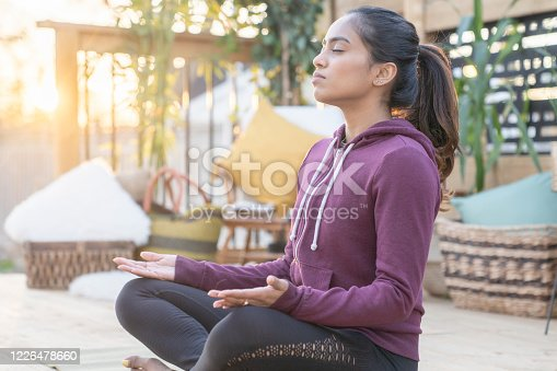 Beautiful mixed race female in her 20's doing relaxing yoga in her backyard while the sunsets behind her.