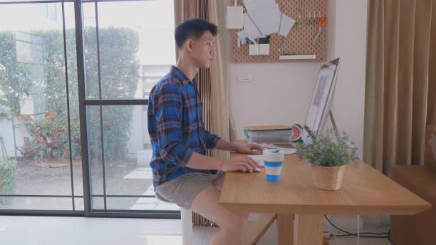 Südostasiatischer Mann arbeitet von zu Hause aus – Foto