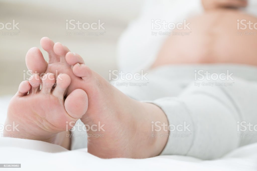 Southeast asian pregnant women with swelling feet, pain foot and lying on bed in the room. Swollen feet and fetal poisoning or toxicity concept stock photo