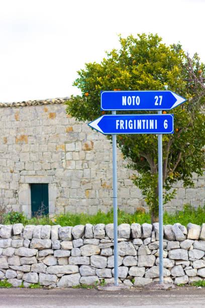 """southeast sicily blue road sign: """"noto 27 km""""; orange tree - cartello stradale italia km foto e immagini stock"""