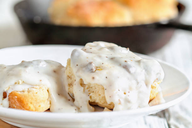 Southern Biscuits and Sausage Gravy American biscuits from scratch covered with thick white sausage gravy. Selective focus with cast iron skillet / pan in the background over a white table. biscuit stock pictures, royalty-free photos & images