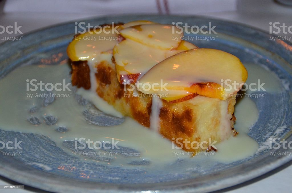 Southern bread pudding with peaches and white chocolate sauce stock photo