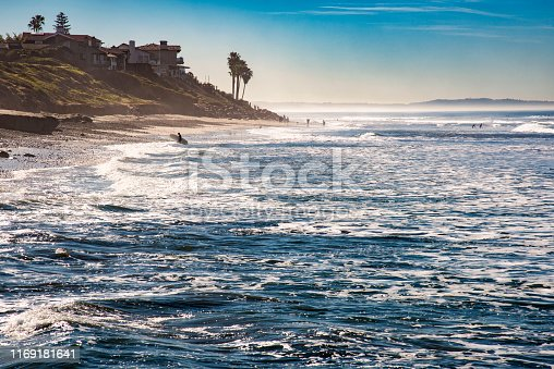 Surfers at the beach in the morning in the northern portion of coastal San Diego County in the city of Carlsbad.