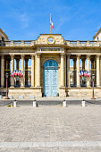 Front view of the southern entrance of the Palais Bourbon, seat of the French National Assembly in Paris, France, decked with french flags on a sunny summer day.