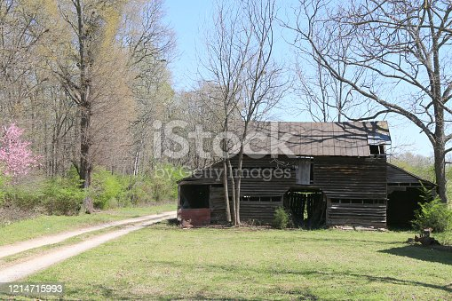 a southern style farm barn with dirt drive and blue sky