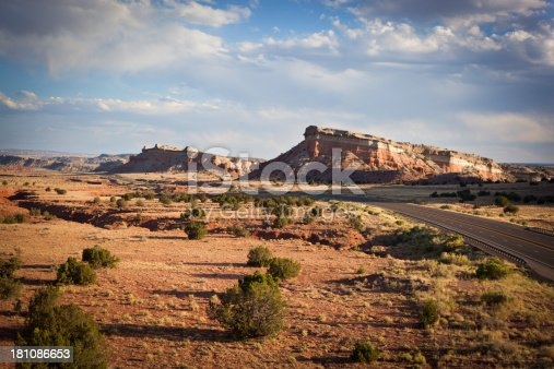 a four lane highway cuts through the desert badlands landscape underneath a cloud filled moody sky. such beautiful nature scenery and travel experience can be found on zia pueblo in new mexico. horizontal wide angle and high angle composition.