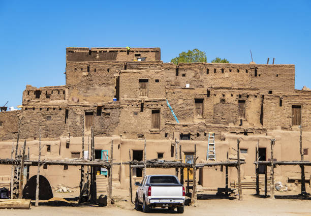 southwestern pueblo where native americans currently live during preparations for their annual harvest celebration - traditional ovens and drying racks and truck parked out in front - native american reservation stock photos and pictures