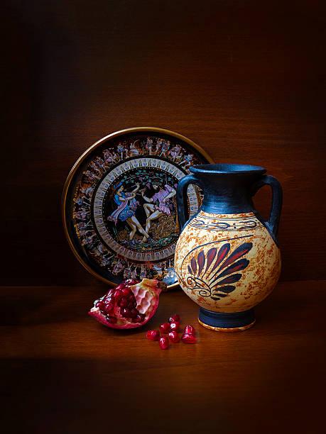 Cтоковое фото Сувенир Ваза Greek, чашка и гранатом на темном фоне
