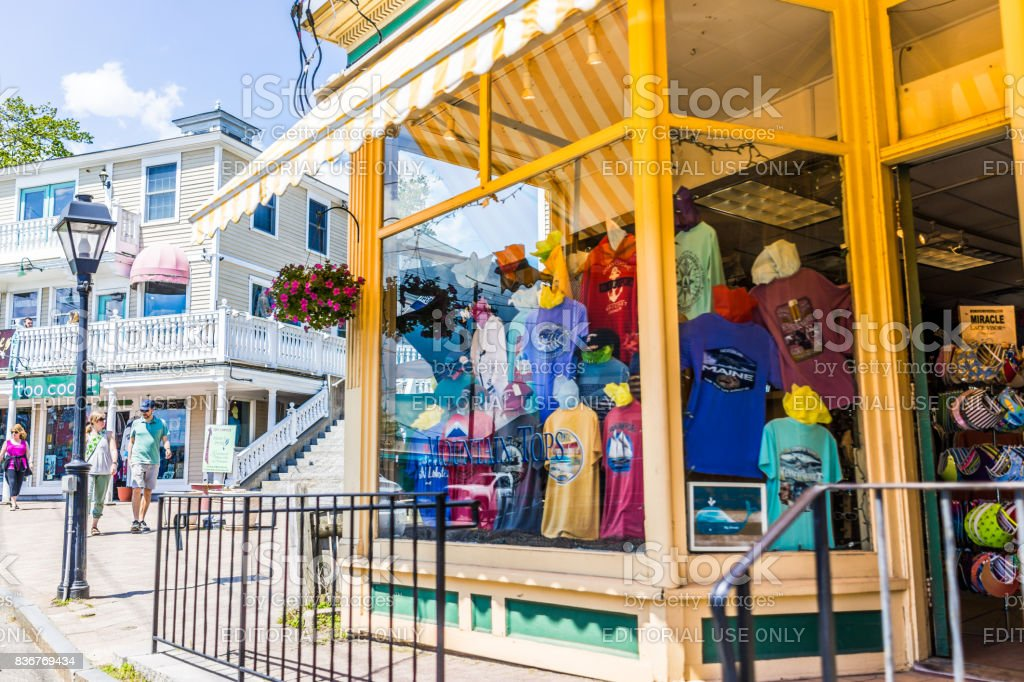 Souvenir shop entrance by sidewalk street with people walking in downtown village during summer day stock photo