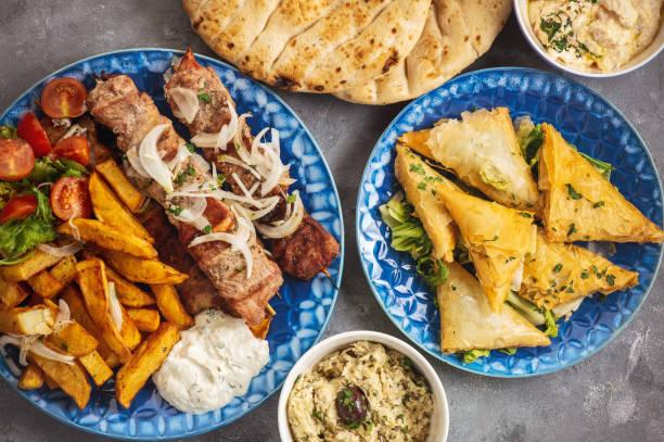 Souvlaki served with fried potatoes, tzatziki dip and pita bread, greek cuisine. stock photo