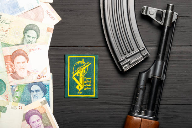 Soviet automaton AK 47 against the backdrop of Iranian money depicting Ruhollah Khomeini and sign of Islamic Revolutionary Guard Corps stock photo