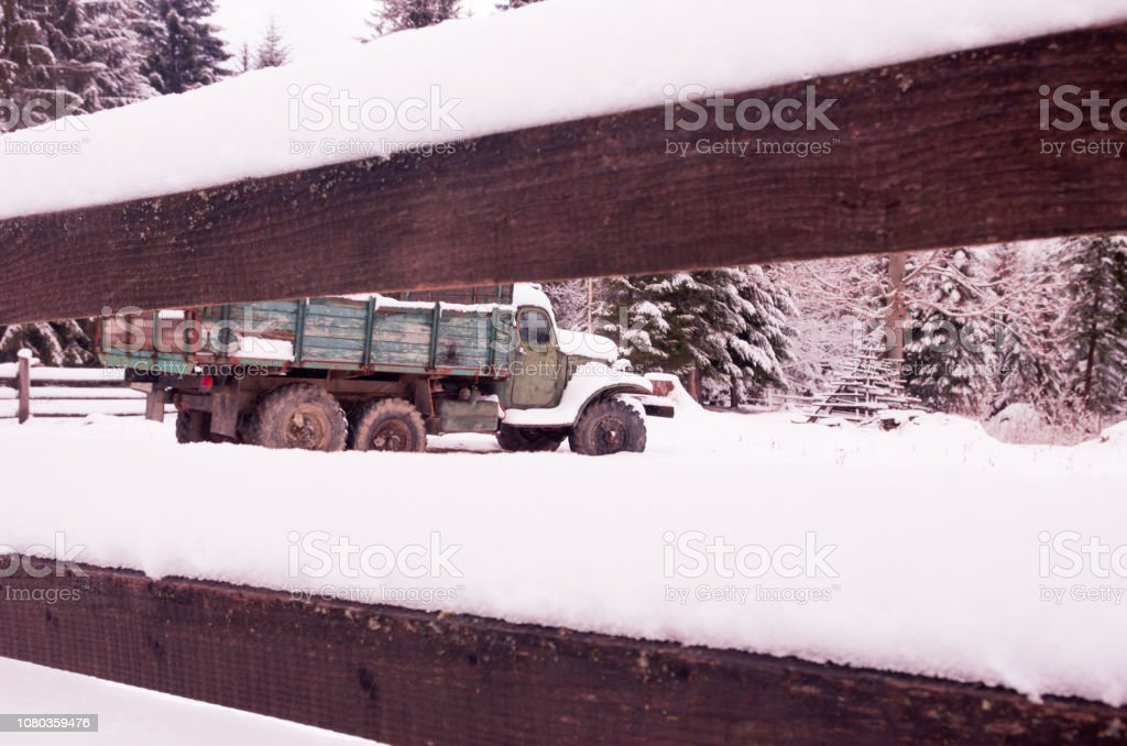 Soviet car behind the fence. The old cargo car. The car is under snow.