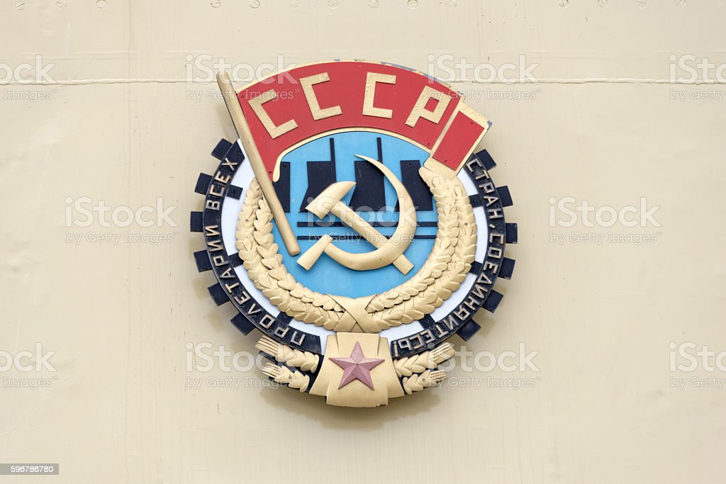 Soviet CCCP emblem with hammer and sickle on a wall stock photo