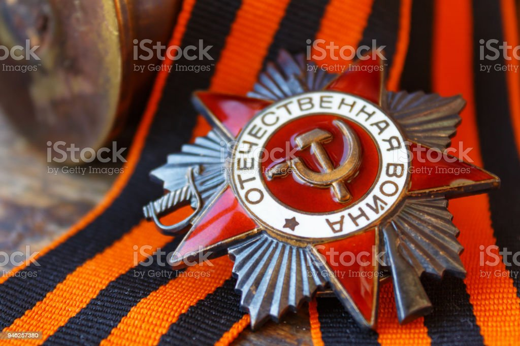 Soviet order of Patriotic War (inscription Patriotic war) with St. George's ribbon and empty shell casings on an old wooden table. May 9 Victory day in the great Patriotic war of 1941-1945 stock photo