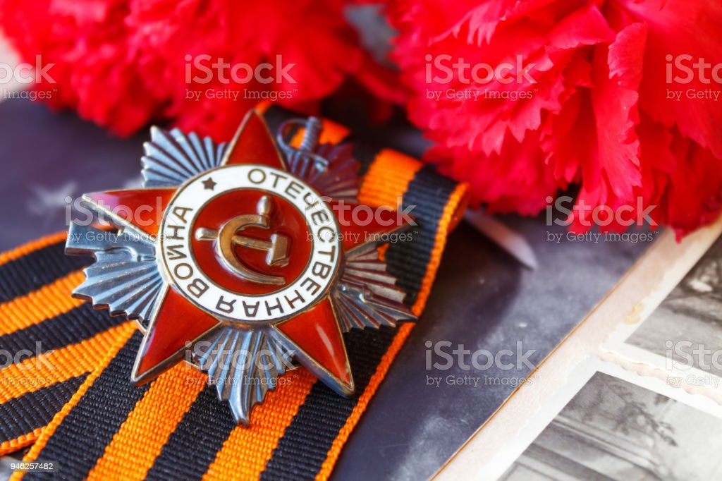 Soviet order of Patriotic war (inscription Patriotic war) with St. George's ribbon and red carnations against the background of old photos. May 9 Victory day in the great Patriotic war of 1941-1945 stock photo