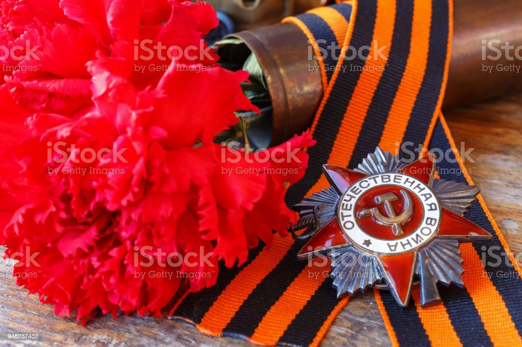 Soviet order of Patriotic war with St. George's ribbon and red carnations on an old wooden table. May 9 Victory day in the great Patriotic war of 1941-1945 stock photo