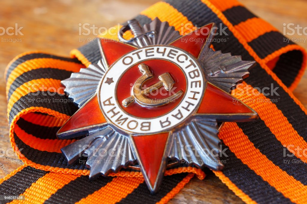 Soviet order of Patriotic War (inscription Patriotic war) with St. George's ribbon on an old wooden table. May 9 Victory day in the great Patriotic war of 1941-1945 stock photo