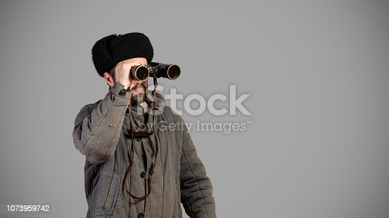 Soviet soldier with binoculars keeps track of the situation, studio shot. Great Patriotic War theme