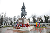 Bucharest, Romania - February 21, 2020: Soviet soldier statue at the Red Army Cemetery in Bucharest during a cold and rainy winter day.