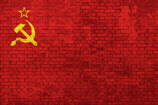 Wall of bricks painted with the Flag of the old Soviet Union, adopted from 12 November 1923 to 15 August 1980. Concept of social barriers, divisions, and political conflicts in 1980s. 3D background.