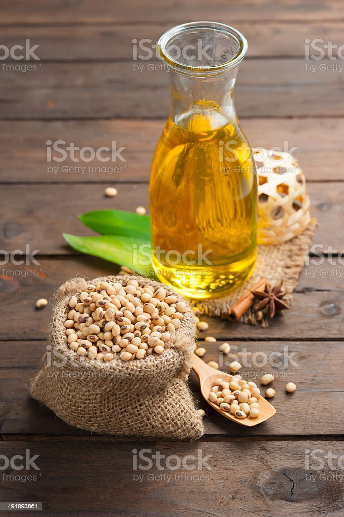 Soy bean and soy oil on wooden stock photo