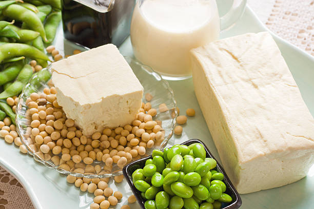 Soy Bean Food and Drink Products Photograph with Several Elements Soy Products. Soy Bean Food and Drink Products Photograph with Several Elements including loose bean,tofu, and soy milk. Full block of tofu.  Half block of tofu sitting on plate of loose soy beans. Green beans in black square bowl. Glass filled with soy milk. soy food stock pictures, royalty-free photos & images