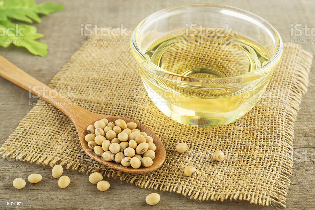 Soy beans and oil on sack stock photo