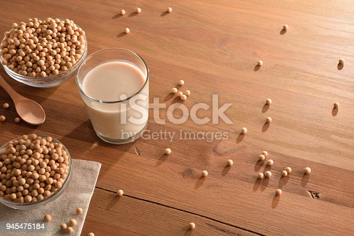 istock Soy milk and grains in containers on wood table elevated 945475184