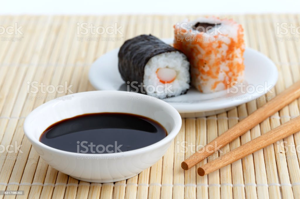 Soya Sauce In White Bowl On Bamboo Mat With Chopsticks And