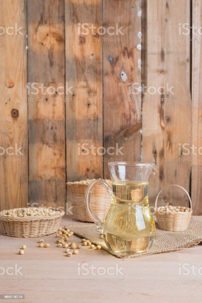 Soybean and soybean oil in jar on wood zbiór zdjęć royalty-free
