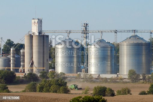Malcom, Iowa, USA - September 9, 2014: Soybeans being harvested with combine in front of rural grain elevator with drying towers, storage bins and train cars transporting grain to end users.