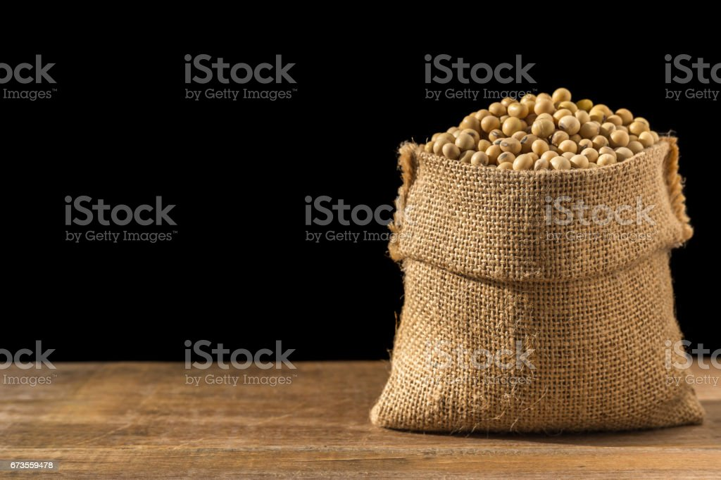 Soybean in small brown sack on wooden table. Isolated on black background royalty-free stock photo