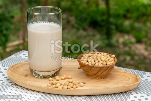 887350996 istock photo Soybean milk or Soy milk in a glass and soy beans in wooden bowl on wooden tray. 1226041310
